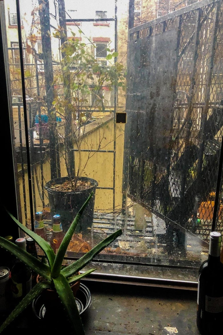 A window to a fire escape facing an ochre courtyard on a rainy day.