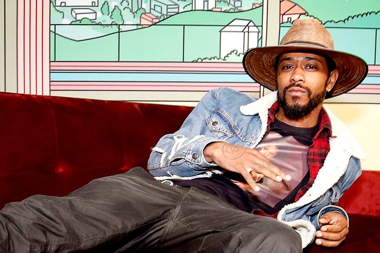 Lakeith Stanfield wearing a hat and relaxing on a couch.