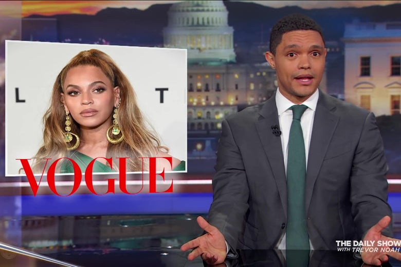 Trevor Noah sits at a news desk; the image over his shoulder is a photo of Beyoncé.