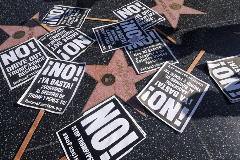 Protest posters are placed at President Donald Trump's star on the Hollywood Walk of Fame.