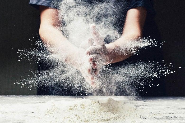 Man spreading flour while making dough.