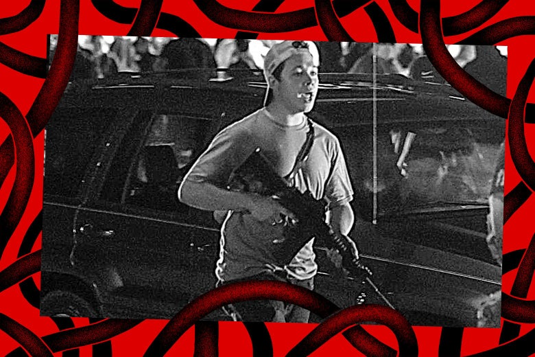 A young man in a T-shirt and backward baseball cap holds an AR-15-style rifle.