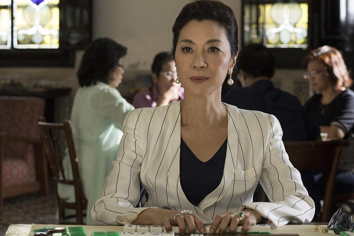Michelle Yeoh, wearing a white pinstripe blazer, sits at a table, handling mahjong tiles.
