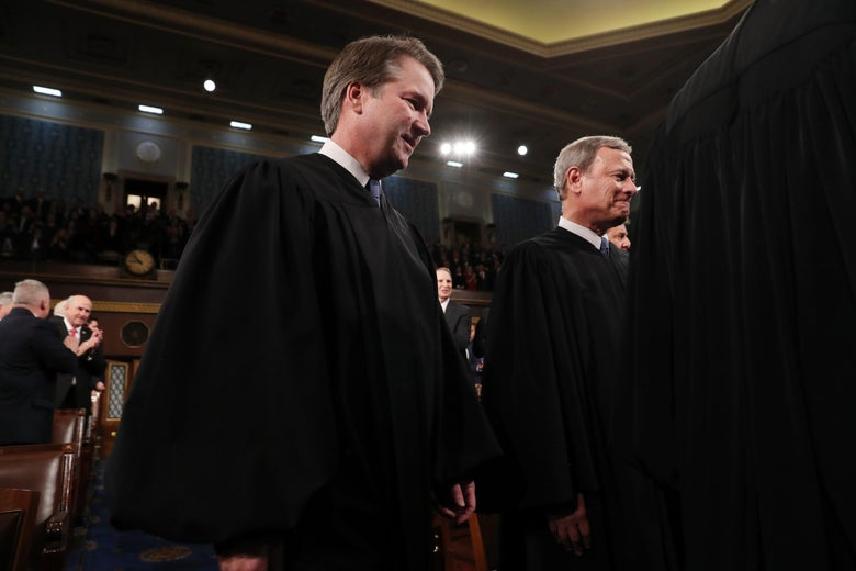 Brett Kavanaugh and John Roberts stand while wearing robes.