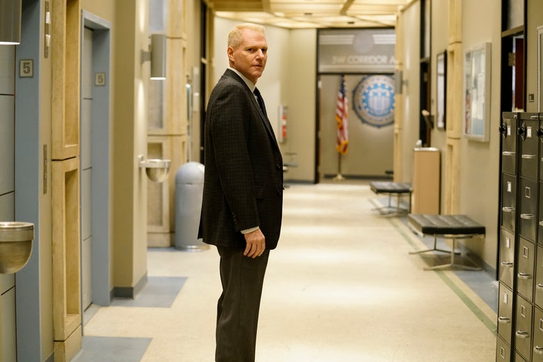 Noah Emmerich as Stan Beeman on The Americans. Emmerich is a white man in fifties with thinning blonde hair and a medium build. He wears brown trousers and a black jacket. The shot shows him from the calves up, in profile. He stands in a hallway.
