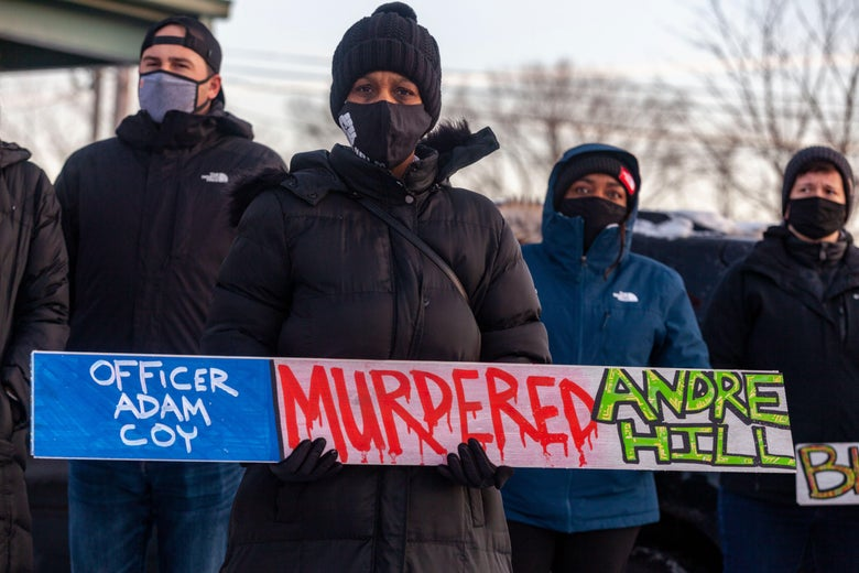 A demonstrator standing in a crowd holds a sign condemning Officer Adam Coy