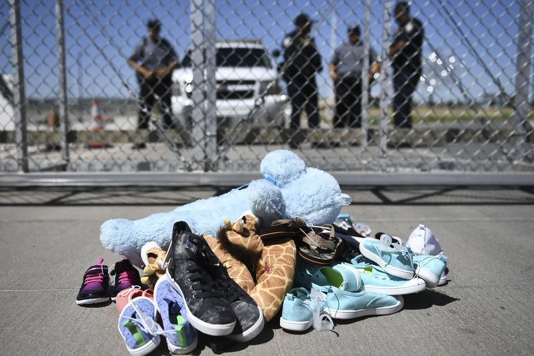A pile of shoes and stuffed animals on the ground in front of a fence behind which security personnel stand guard beside an SUV