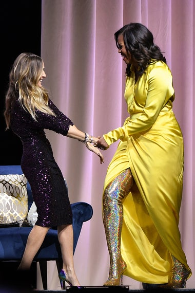 Michelle Obama greets Sarah Jessica Parker with a handhold and a smile onstage, wearing her tall gold glittery boots.