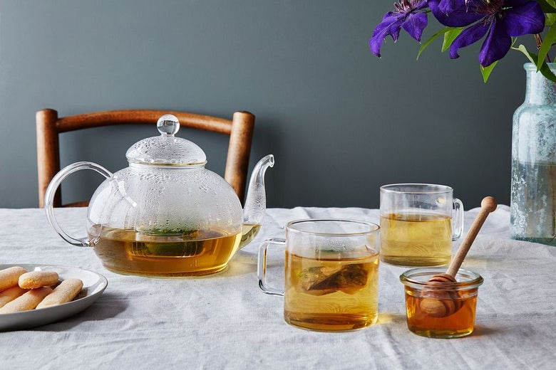 Clear glass teapot and teacups filled with golden-hued tea next to a glass honey jar with a dipper in it, a plate of tea cookies, and a flower vase on a table