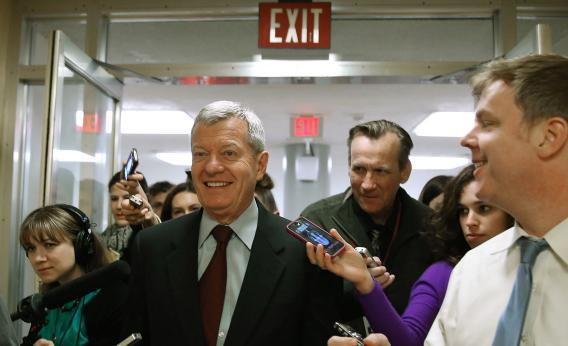 Sen. Max Baucus is trailed by reporters April 23, 2013, on Capitol Hill in Washington, D.C.