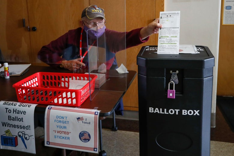 An election worker wearing a mask reaches across the table he's sitting at to drop a ballot in the slot of a ballot box