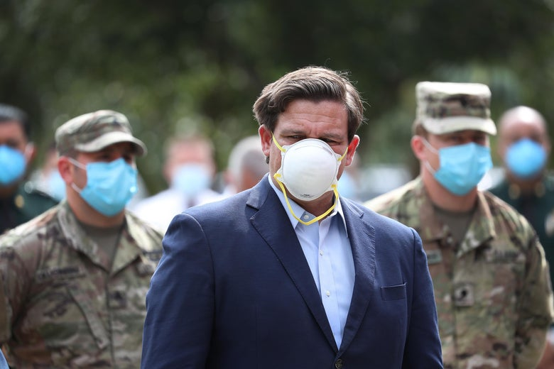Ron DeSantis, wearing a mask, stands in front of National Guard members wearing masks
