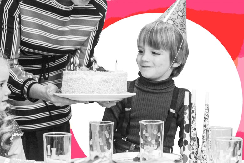 A kid wearing a party hat smiles as an adult brings him a cake and another kid looks on at a birthday party