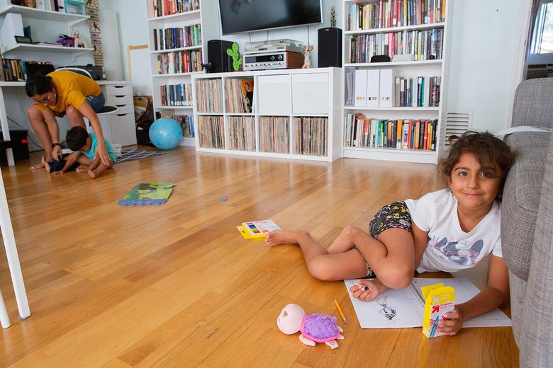 A little girl sitting on the ground with her art supplies smiles at the camera. On the other side of the room, her mother reaches down to her son, who's sitting on the floor. In the background are bookshelves and a TV.