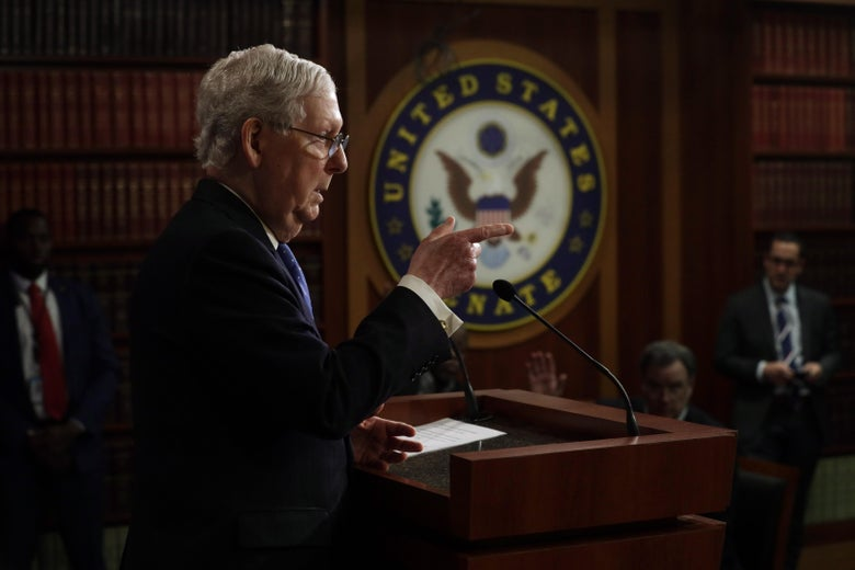 Mitch McConnell speaks at a podium at a press conference