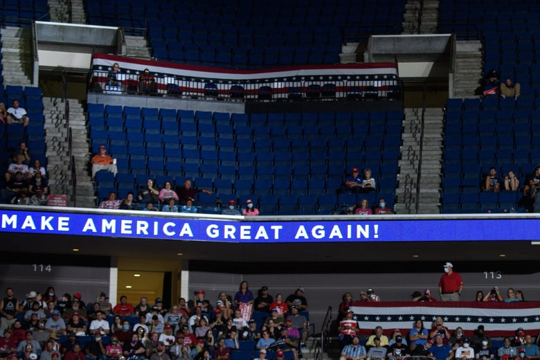 "The largely empty upper section of an arena above an electronic sign that says ""Make America Great Again."""