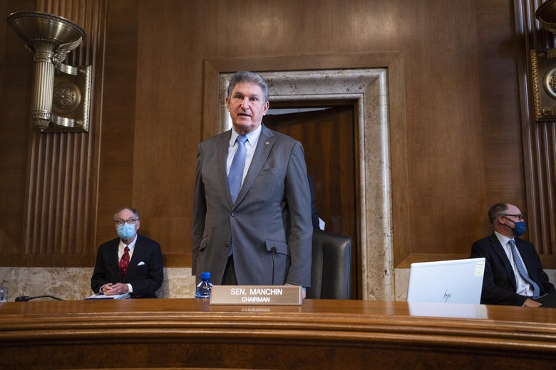 Manchin stands and speaks during a hearing