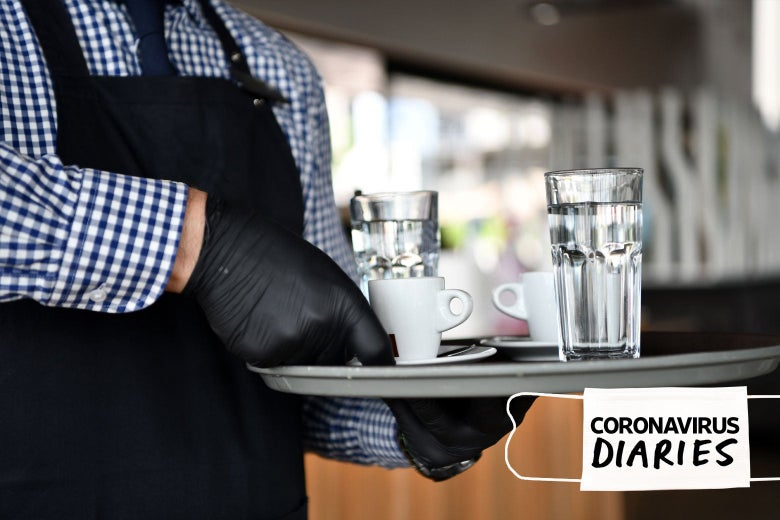 A waiter wearing gloves holds a tray of cups of water and espresso.