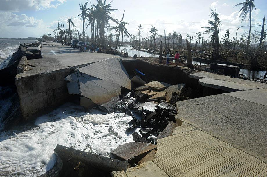 Residents cross a collapsed highway caused by the storm surge in Palo, eastern island of Leyte on November 10, 2013, three days after devastating Super Typhoon Haiyan hit the area on November 8.