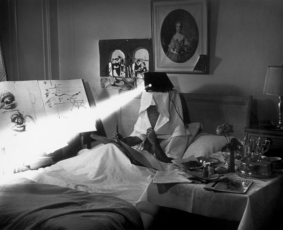 """Spain. Salvador Dali in bed in 1964, projecting pieces of dirty paper """"to stimulate his inspiration."""""""