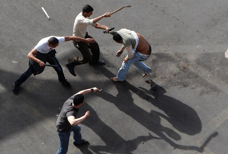 Plainclothes security personnel use batons to beat a protester at Cairo's Tahrir Square March 3, 2013.
