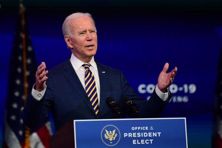 Joe Biden raises his hands while speaking at a lectern.