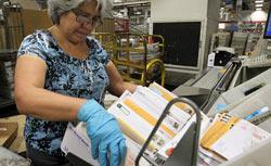 U.S. Postal Service worker Magda Aguirre places mail into a sorting machine at the U.S. Post Office sort center. Click image to expand.