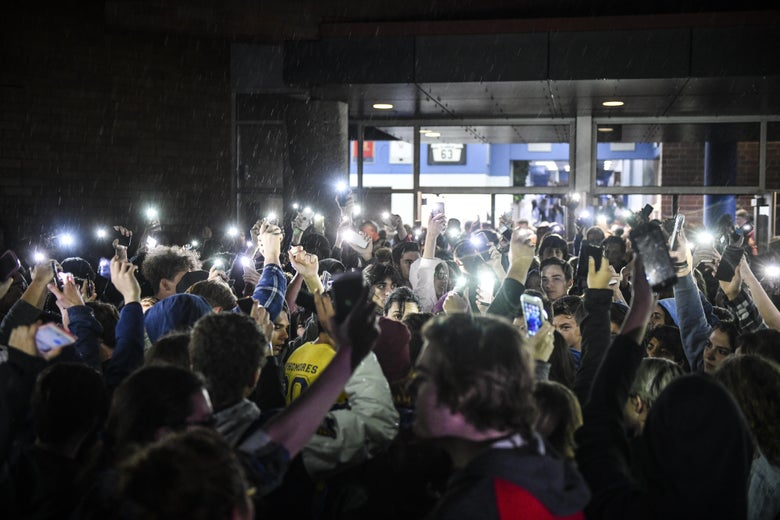 Students hold up their lit phones as they exit a high school.