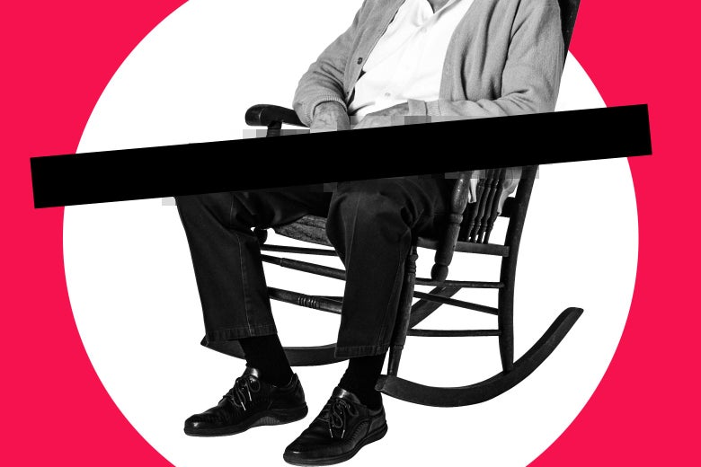 A man sits in a rocking chair. There is a black bar over his lap.