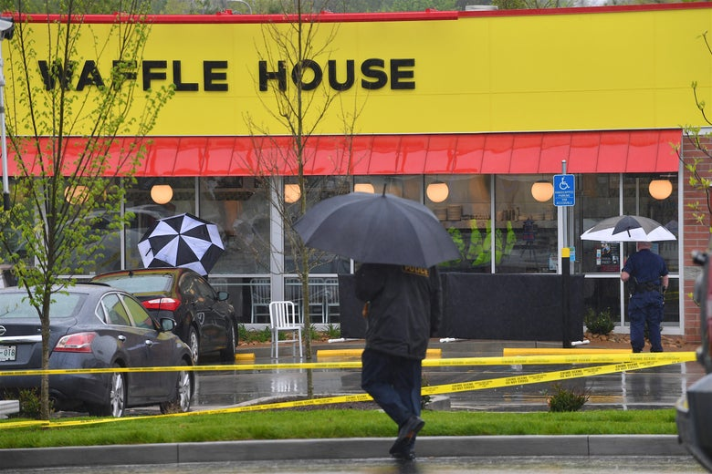 Caution tape and police officers holding umbrellas are seen outside the Waffle House.