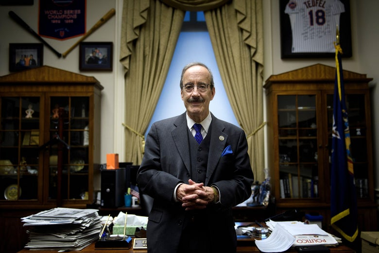 Eliot Engel posing in his office, surrounded by baseball memorabilia.