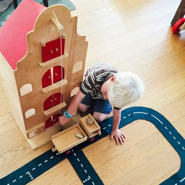 Child playing with wooden dollhouse.