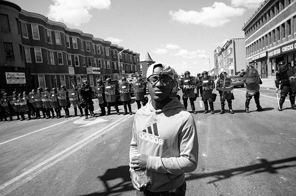 A young man stands in front of the line of police officers on North Avenue, Baltimore, April 29, 2015.