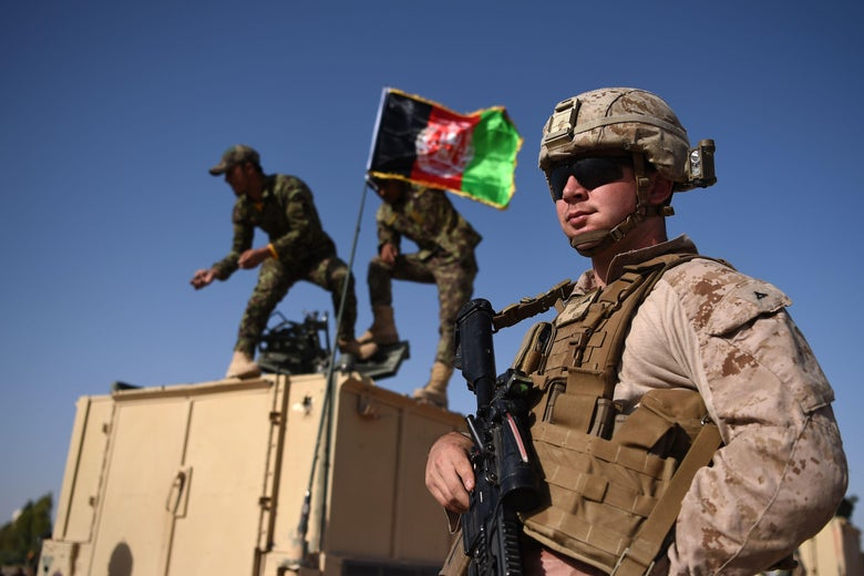 A U.S. Marine looks on as Afghan National Army soldiers raise the Afghan flag on an armed vehicle.