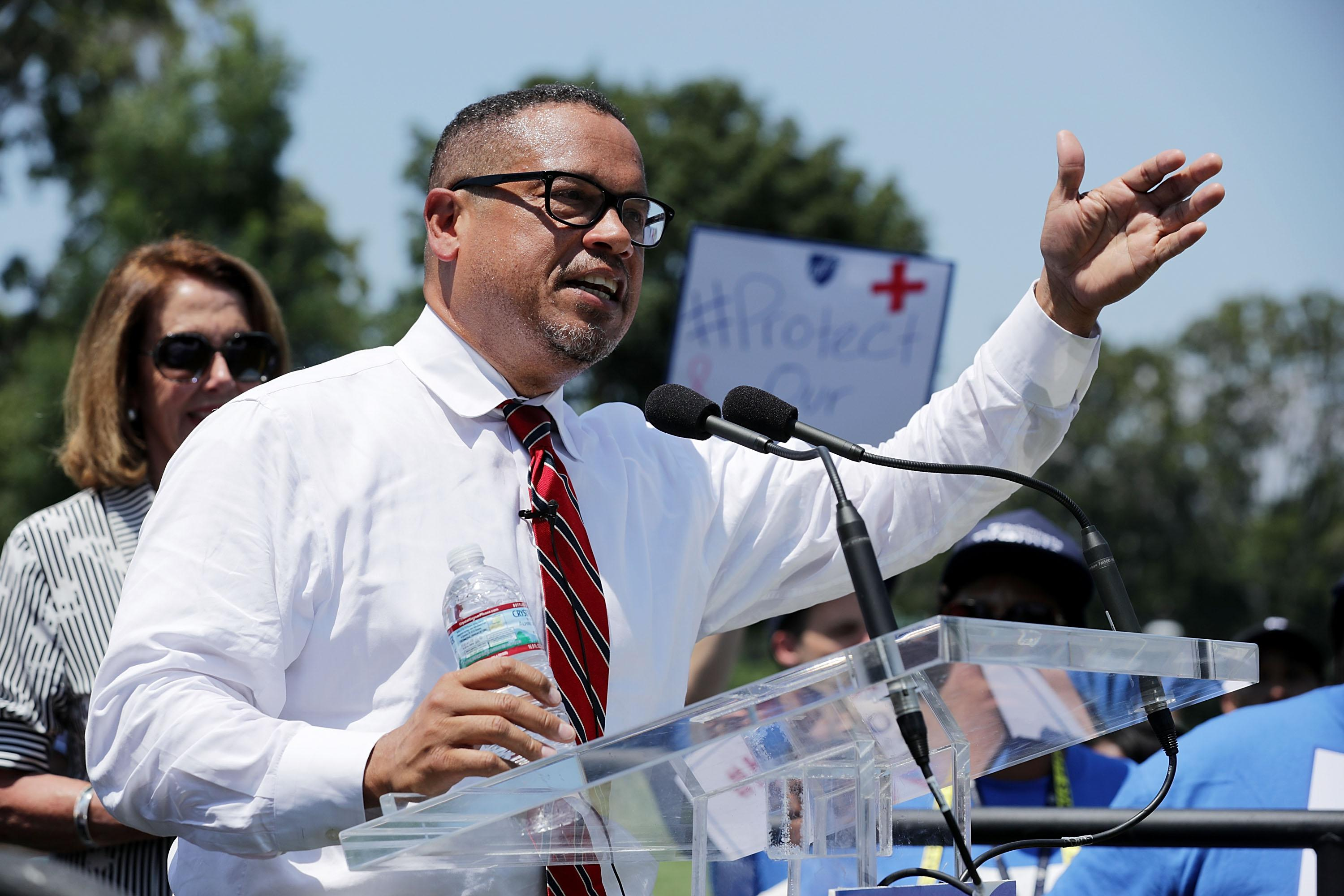 Ellison, in a white shirt and red tie, raises his arm to gesture to a crowd as he speaks. Behind him, people wave signs.