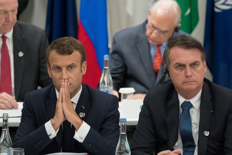 Emmanuel Macron and Jair Bolsonaro sitting next to each other.