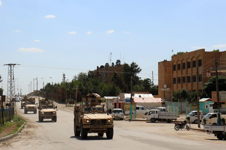 Armored vehicles drive down a road in Syria.