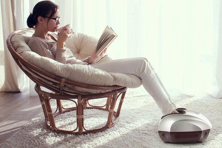 Woman reclining with her feet inside a Belmint foot massager.