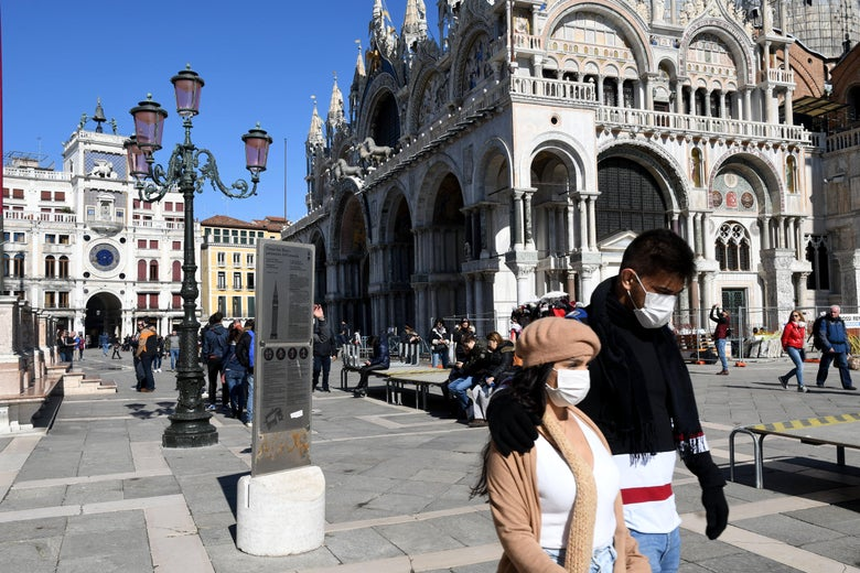 Tourists wearing a protective face mask walk on San Marco square in Venice on March 8, 2020.