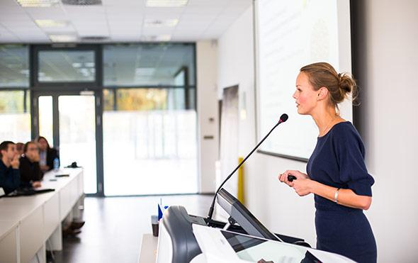 Woman giving speech at business conference.