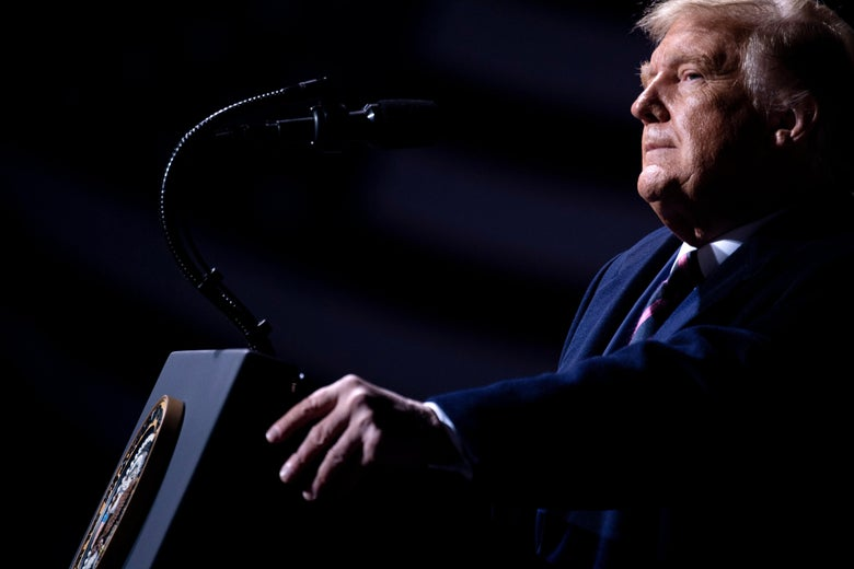 Trump pauses, gripping the podium, while speaking