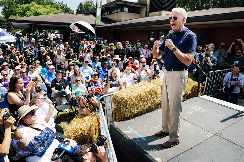 Joe Biden, wearing aviators, a polo, and khakis, stands on a stage near hay bales.