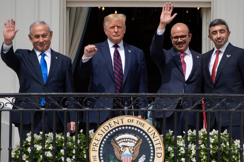 The four men standing in tight formation waving from a balcony. Trump is holding up his fist.