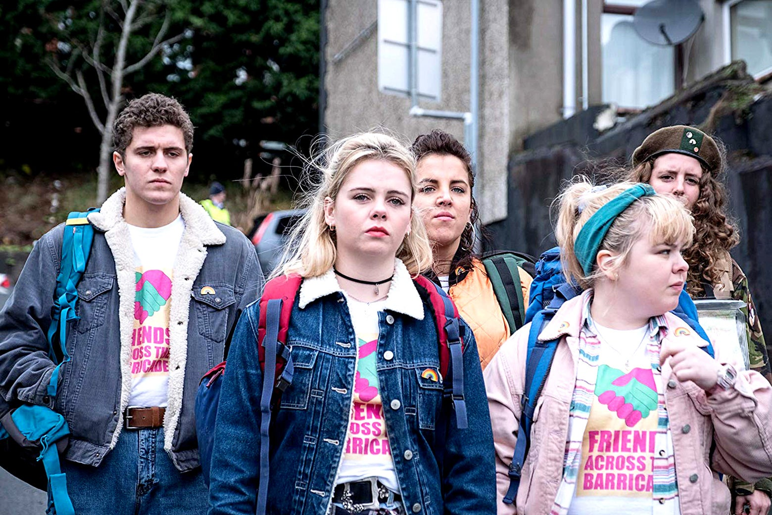 """A group of teens in '90s Ireland wearing """"Friends Across the Barricade"""" T-shirts, in a scene from Derry Girls."""