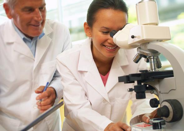 Older man approaching younger woman engaged in microscopic study.