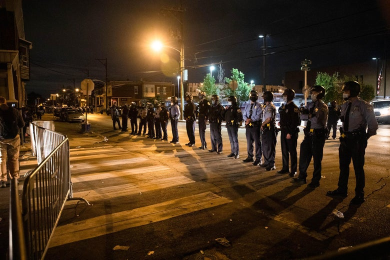A line of police officers in masks behind a barrier at night.
