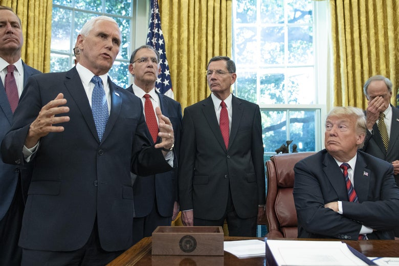 Vice President Pence speaks to the press pool as President Trump looks on in the Oval Office on October 23, 2018.