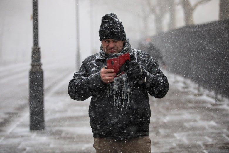 A man takes pictures on his phone during a snow flurry.