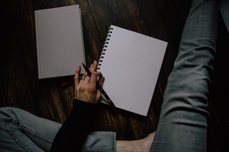A view from above of a person's legs sitting on a floor, pen in hand, in front of an empty open notebook and closed book.
