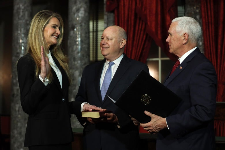 Loeffler smiles and holds up her right hand as she puts her left hand on a Bible held by her husband, with Pence standing beside them.